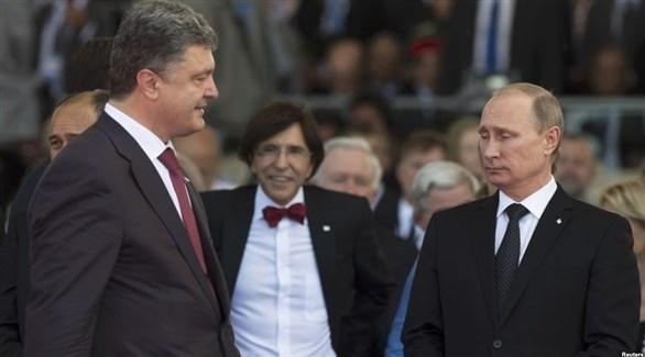 الرئيسان الروسي بوتين والأوكراني بوروشينكو وبينهما رئيس الحكومة البلجيكية السابق (أرشيف)