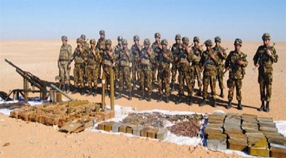 جنود من الجيش الجزائري أمام ذخائر وأسلحة محجوزة في الصحراء (أرشيف)