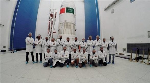 فريق القمر الصناعي السعودي أمام الصاروخ الذي سيحمل القمرين الصناعيين إلى الفضاء (هي)