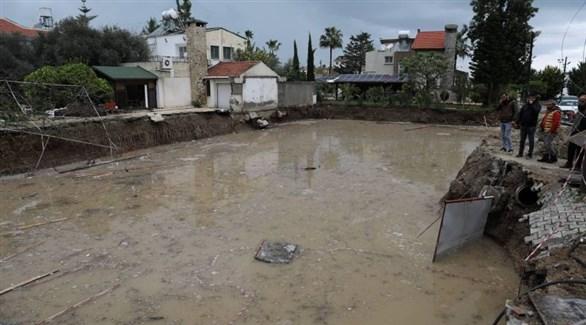 قبارصة ينظرون إلى تجمع المياه في منطقة كيرينيا (رويترز)
