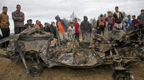 فلسطينيون حول مركبة الوحدة المتسللة التي دمرتها غارة إسرائيلية على خان يونس (أرشيف)