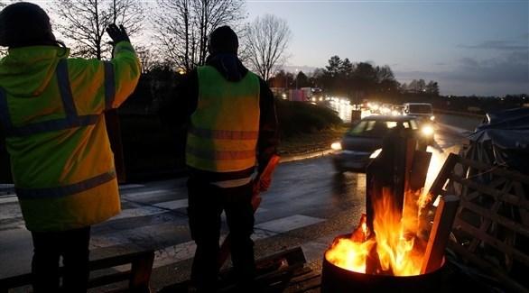 محتجون قبالة أحد الشوارع في بلجيكا (رويترز)