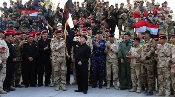 رئيس الوزراء العراقي السابق حيدر العبادي رافعاً العلم العراقي في الموصل بعد إعلان النصر على داعش (أرشيف)