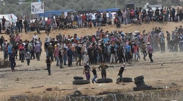 محتجون فلسطينيون عند الشريط الفاصل بين قطاع غزة وإسرائيل (أرشيف)