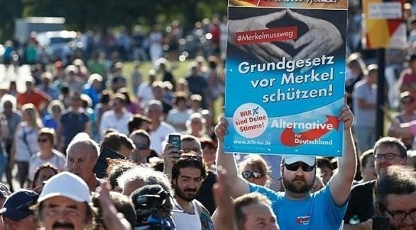 مؤيد لحزب البديل من أجل ألمانيا يرفع لافتة كُتب عليها