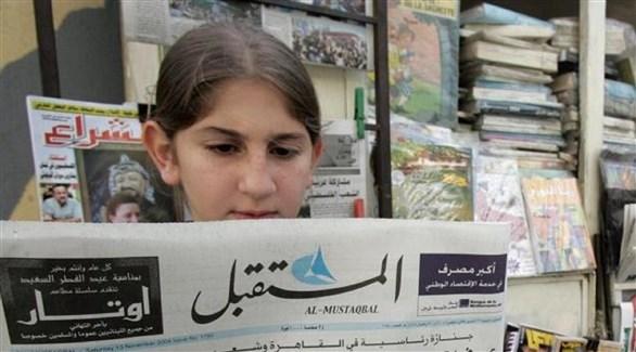 فتاة لبنانية تطالع صحيفة
