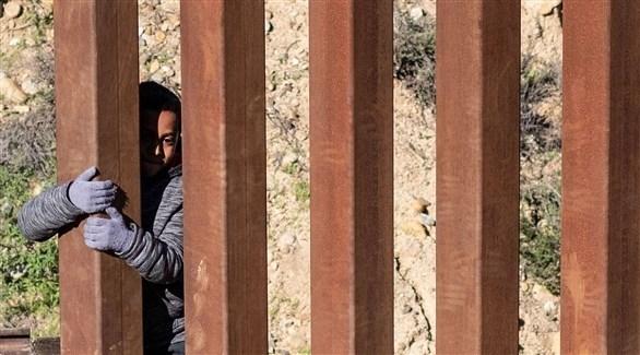 مهاجر خلف السياج الفاصل بين المكسيك وأمريكا (أ ف ب)