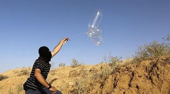 ملثم فلسطيني يطلق بالوناً محملاً بمواد حارقة باتجاه إسرائيل جنوب قطاع غزة (أرشيف)