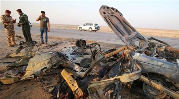 قوات أمنية عراقية تحيط بسيارة متفحمة (أرشيف)
