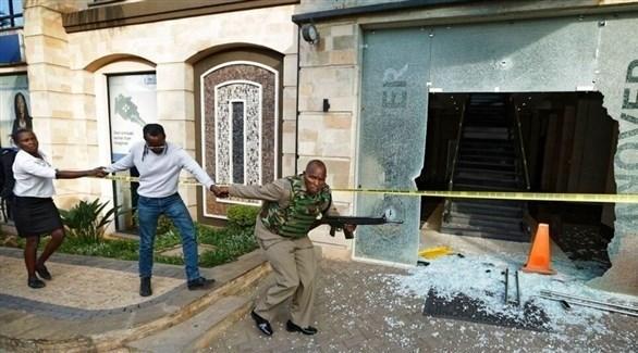 رجل أمن كيني يحاول إبعاد مواطنيه عن مكان الهجوم الإرهابي في نيروبي (تويتر)