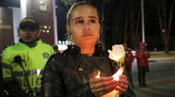 كولومبية تحمل شمعة حداداً على ضحايا التفجير في بوغوتا (انفو باي)