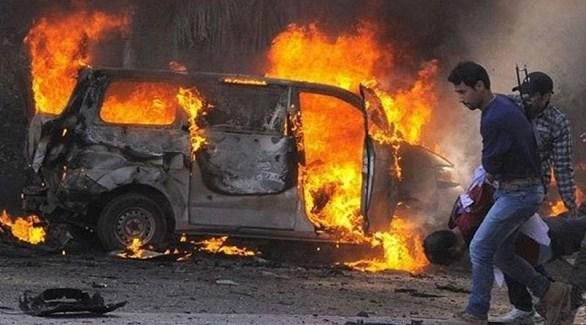 سوريون قرب سيارة مشتعلة بعد تفجير سابق (أرشيف)