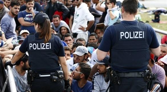 شرطيان ألمانيان يواجهان مجموعة من طالبي اللجوء في (أرشيف)