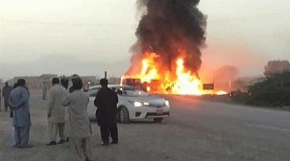 باكستانيون ينظرون إلى الحافلة المحترقة بعد انقلابها (تويتر)