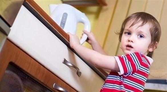 طفل يمسك بمسخن ماء (أرشيف)