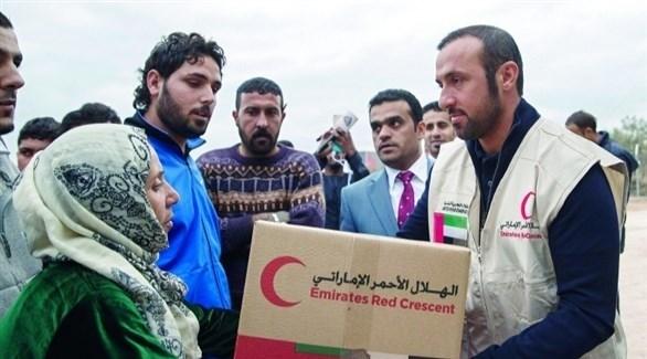 متطوع من الهلال الأحمر الإماراتي يقدم مساعدات لنازحين سوريين في اليونان (أرشيف)