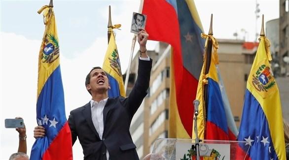 رئيس البرلمان الفنزويلي خوان غوايدو يرفع صورة بطل الاستقلال سيمون بوليفار (أ ف ب)