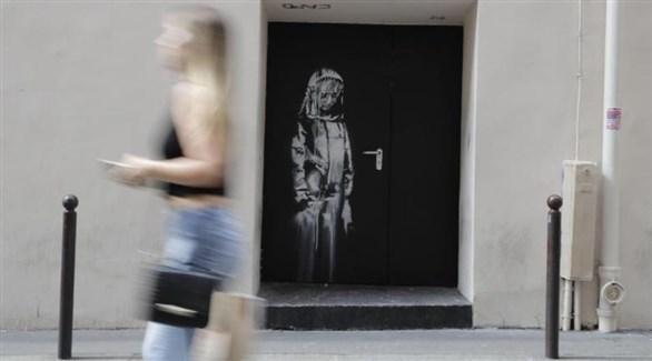 لوحة بانكسي المسروقة على باب طوارئ مسرح باتاكلان في باريس قبل سرقتها (تويتر)