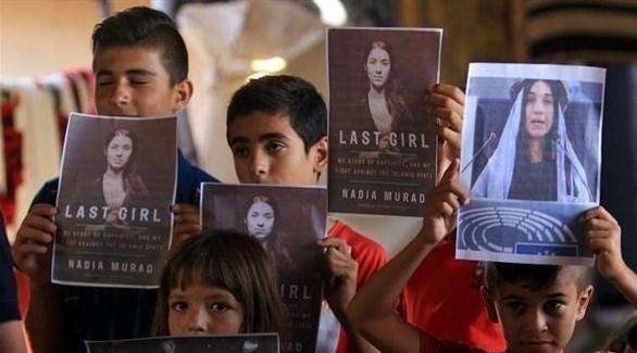 أطفال إيزيديون يحملون صور نادية مراد صاحبة جائزة نوبل للسلام (أرشيف)