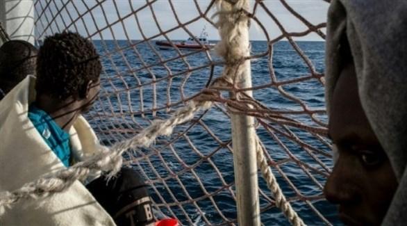 مهاجرون على متن السفينة سي ووتش 3 وقبالتهم سفينة لخفر السواحل الإيطاليين (أف ب)