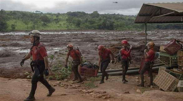 عمال الإنقاذ في محيط السد المنهار بالبرازيل(رويترز)