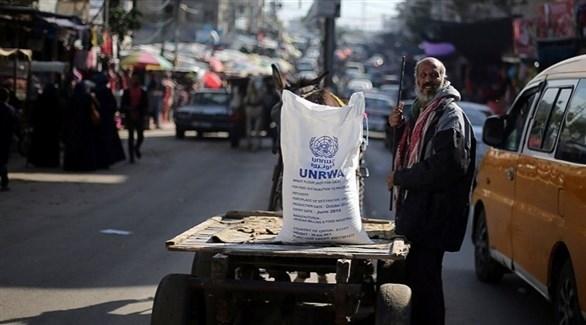 مسن فلسطيني مع كيسٍ بشعار أونروا على عربة (أرشيف)