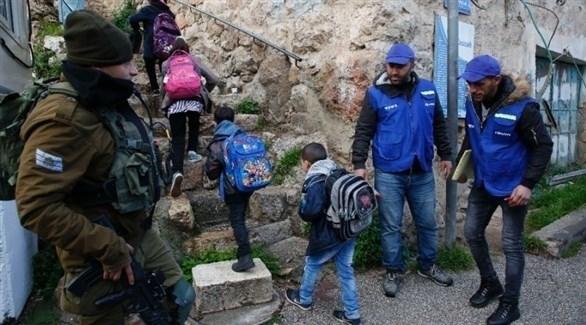 شبان من الخليل يرافقون أطفالاً فلسطينيين متوجهين لمدارسهم (تويتر)