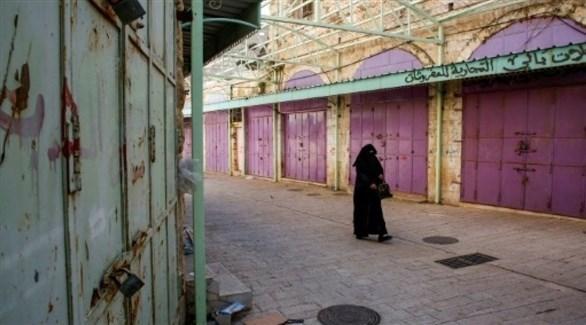 امرأة تسير أمام متاجر مغلقة خلال إضراب في مدينة الخليل بالضفة الغربية (أ ف ب)