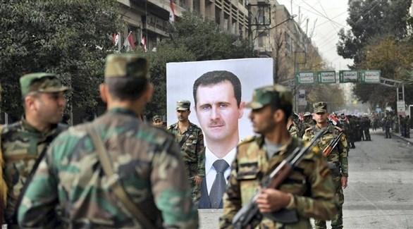 عناصر من الجيش السوري وبدت صورة الأسد بجانبهم (أرشيف / رويترز)