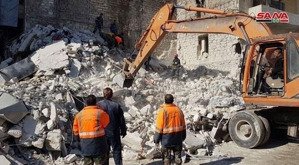 جرافة وعمال إنقاذ قرب المبنى المنهار في حلب (سانا)