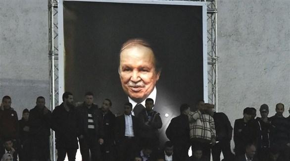 جزائريون يقفون بمحاذاة صورة ضخمة للرئيس الجزائري (أرشيف)