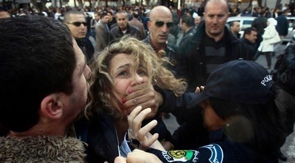 شرطية تعتقل إحدى المتظاهرات في الجزائر (EPA)