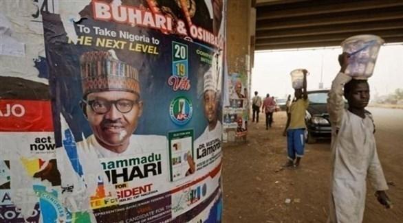 صور مرشحي الانتخابات الرئاسية في نيجيريا على الجدران (أ ف ب)