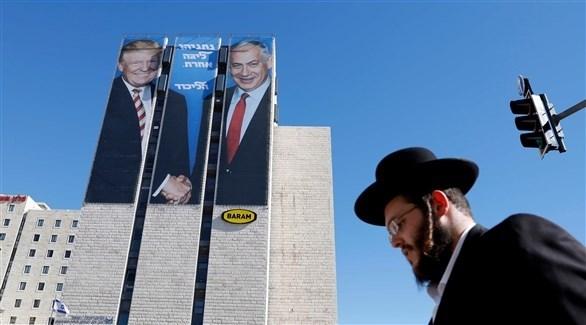 حاخام يهودي يمر بجانب صورة نتانياهو مع ترامب (اي بي ايه)