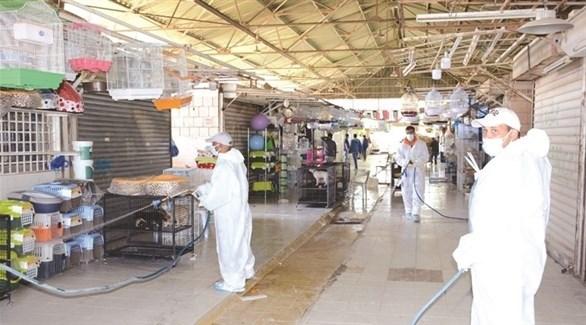 عمال يُطهرون سوقاً في الكويت بعد إعدام طيور مصابة (الراي)
