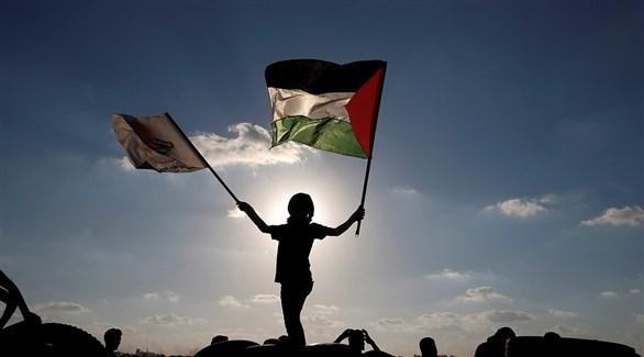 متظاهرة ترفع العلم الفلسطيني (أرشيف)