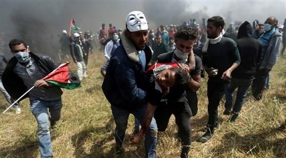 متظاهرون يحملون مصاب بع إصابته في مسيرات العودة (أرشيف)