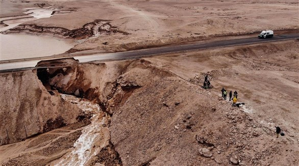 عمال إنقاذ يعاينون ما تبقى من طريق تضرر مع الأمطار (أ ف ب)