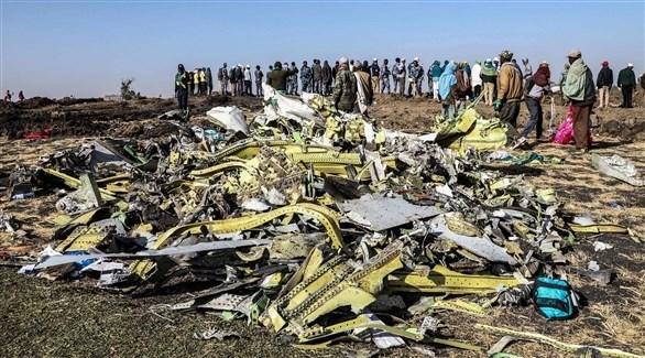 مجموعة من الناس تقف قبالة حطام الطائرة الإثيوبية (أ ف ب)