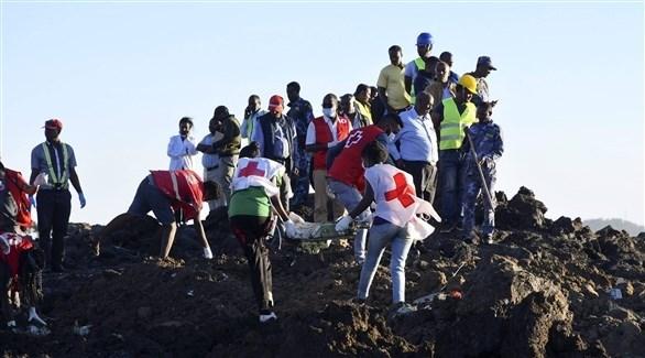 عمال الانقاذ ينتشلون الجثث من مكان تحطم الطائرة