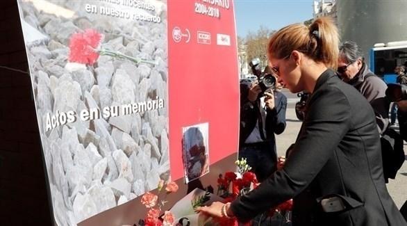 إسبانية تضع زهوراً في ساحة بويرتا ديل سول بمدريد تكريماً لضحايا الهجوم الإرهابي (إ ب ا)