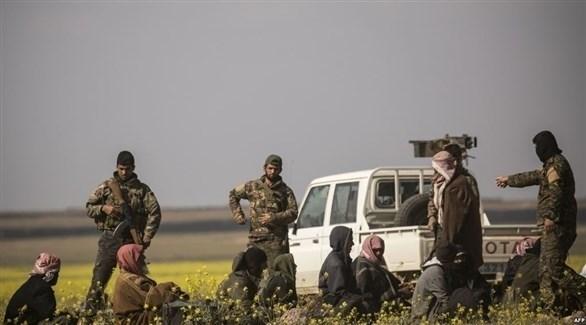 عناصر من قوات قسد مع رجال غادروا الباغوز ويشتبه في انتمائهم لداعش (أ ف ب)
