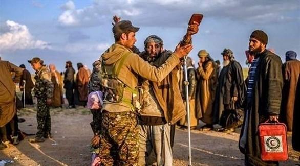 جنود من قوات سوريا الديمقراطية يفتشون مقاتلين من تنظيم داعش بعد استسلامهم (تويتر)