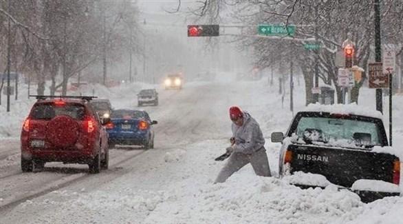 امريكي يحاول إخراج سيارته التي علقت بالثلوج (وكالات)
