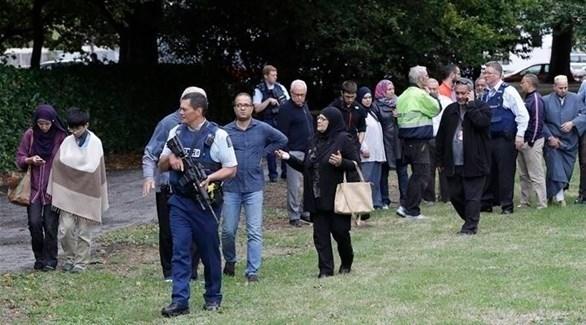 أفراد من الشرطة مع بعض الناجين خارج مسجد النور في نيوزيلندا (تويتر)