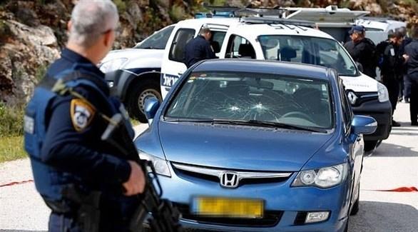 شرطي إسرائيلي أمام سيارة أصيبت بالرصاص اليوم الأحد في الضفة الغربية (تويتر)
