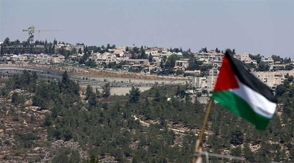 علم فلسطيني وفي خلفية مستوطنة إسرائيلية في الضفة الغربية (أرشيف)