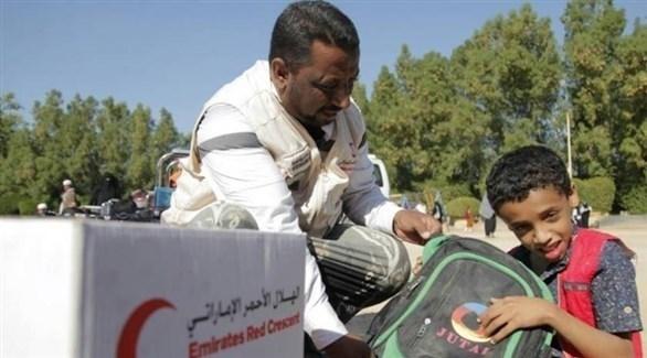 موظف بالهلال الأحمر الإماراتي يوزع مساعدات لطلبة يمنيين (أرشيف)