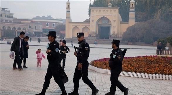 عناصر من الشرطة تمر بجانب الساحة العامة في شينجيانغ (أرشيف / أ ب)