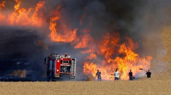 إسرائيليون يكافحون حريقاً سبّبه بالون حارق من غزة (أرشيف)
